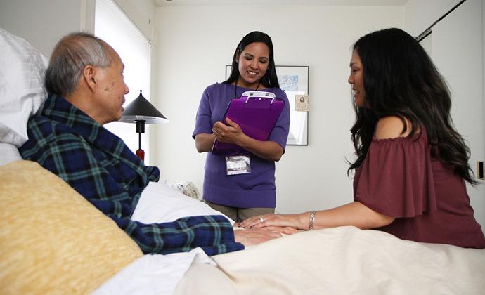 Isang nurse ng VITAS na nakikipag-usap sa isang pasyenteng nakahiga sa kama, at sa kanyang anak na babae