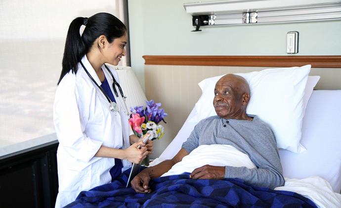 Nakikipag-usap ang isang doctor ng VITAS sa isang pasyenteng nakahiga sa kama