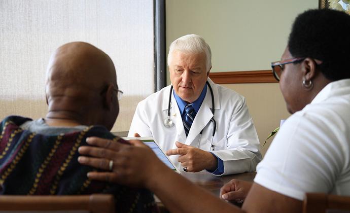 Nagbabahagi ng impormasyon ang isang doctor sa VITAS sa pamamagitan ng isang tablet sa isang mag-asawang nakaupo sa kanyang opisina