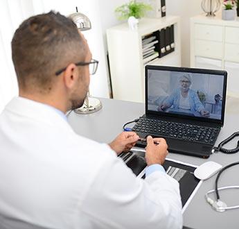 一名健康療護專業人員通過筆電進行視訊會議與一名婦女交談
