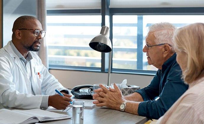 Nakikipag-usap ang doctor sa isang mag-asawa sa desk sa kanyang opisina