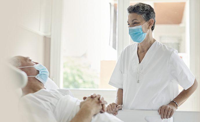 Un clínico habla con un paciente que está recostado en la cama
