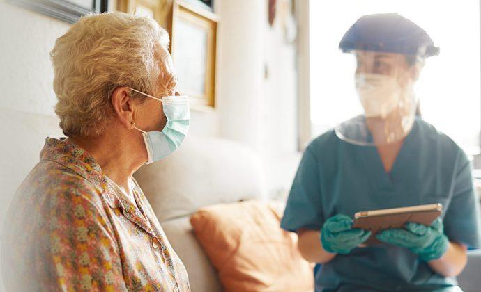 Una médica habla con una paciente sentadas en un sofá.