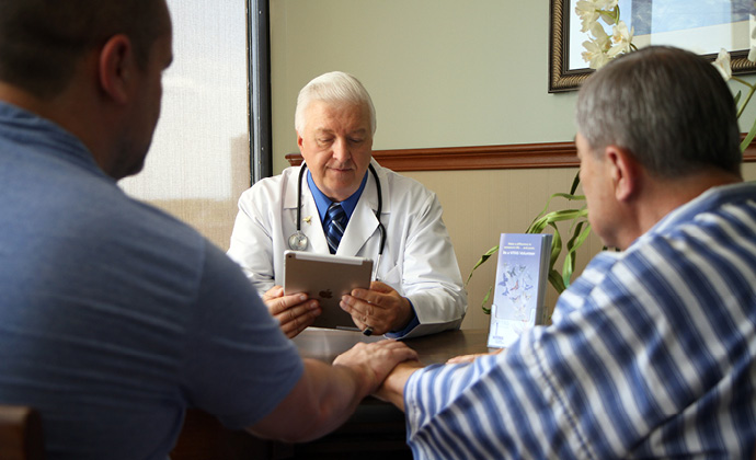 A physician consults an iPad while talking with two other men at a table