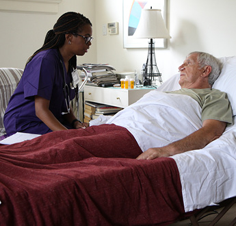 VITAS provider talks with a man lying in bed and using breathing tubes