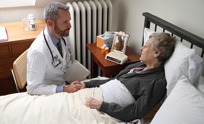Nakikipag-usap ang isang doctor sa isang babaeng nakahiga sa kama atat nakahawak siya sa kamay nito