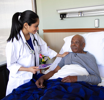 A VITAS physician holding a tablet checks on a patient as he sits up in bed