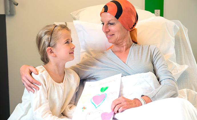 女士坐在床上對著小女孩微笑,小女孩向她展示自己畫的圖畫
