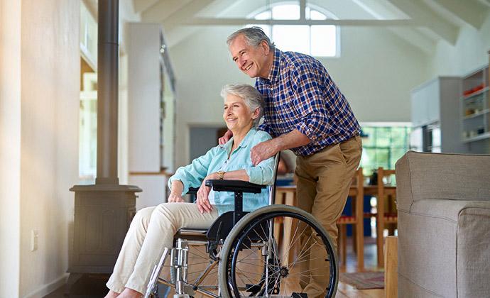 Una mujer en silla de ruedas mira por la ventana, sonriendo, mientras su esposo la acompaña
