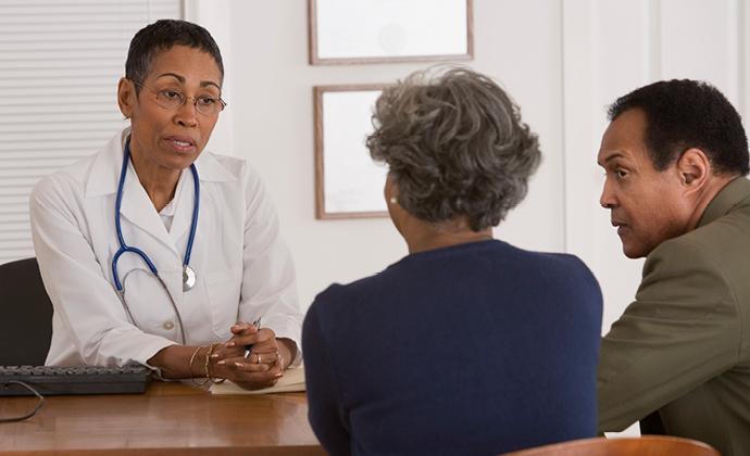 Isang mag-asawa na nakikipag-usap sa kanilang doctor sa isang opisina