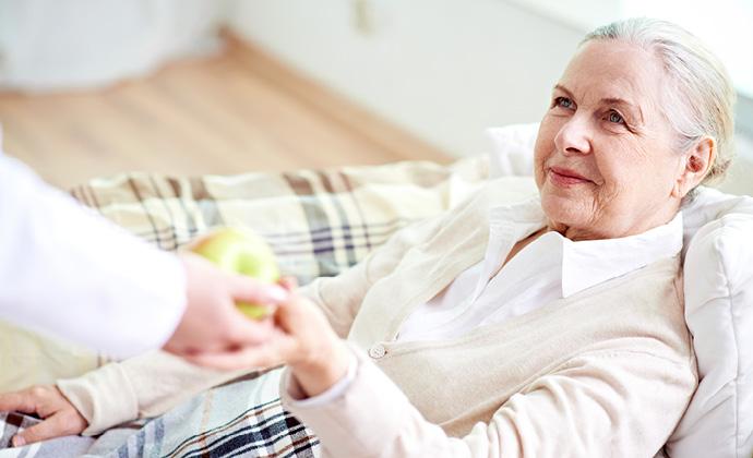 Một ngườiđang đưaquả táo chongười phụ nữngồi trên ghế sofa