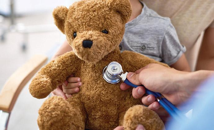 小朋友拿著一個泰迪熊,旁邊的護士拿著聽診器為小熊聽診