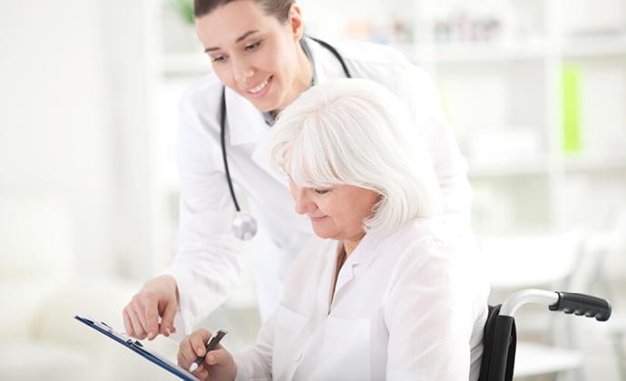 醫師與坐在輪椅上的女士討論一份文件