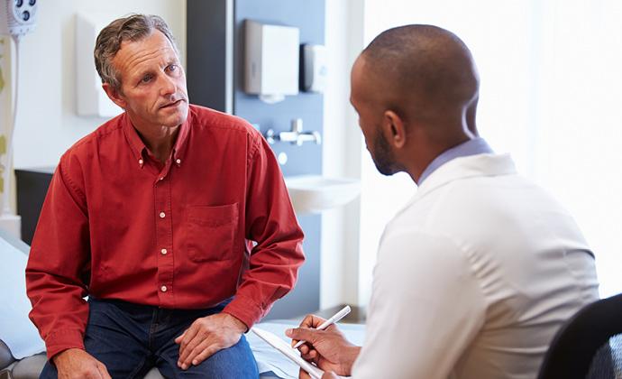 醫師在診療室內與一位男士談話