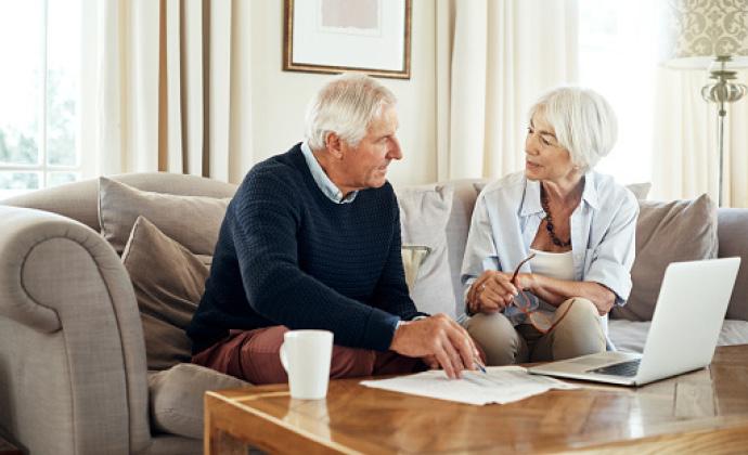 Una pareja en un sofá mira unos papeles y una laptop, sentados junto a una mesa de café