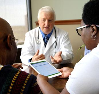 一位醫師坐在桌旁與看著平板電腦的兩人說話