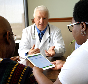Ang isang doktor na nakaupo sa isang mesa ay nakikipag-usap sa dalawang tao habang nakatingin sila sa isang tablet