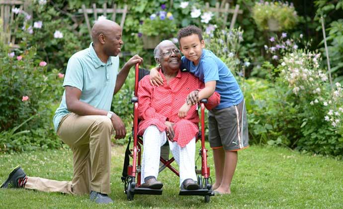 Yinayakap ng isang babaeng nakaupo sa wheelchair ang kanyang apong lalaki, habang naaaliw sila sa hardin sa labas