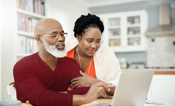 Un hombre con una laptop en la mesa de la cocina mientras su esposa mira a la pantalla