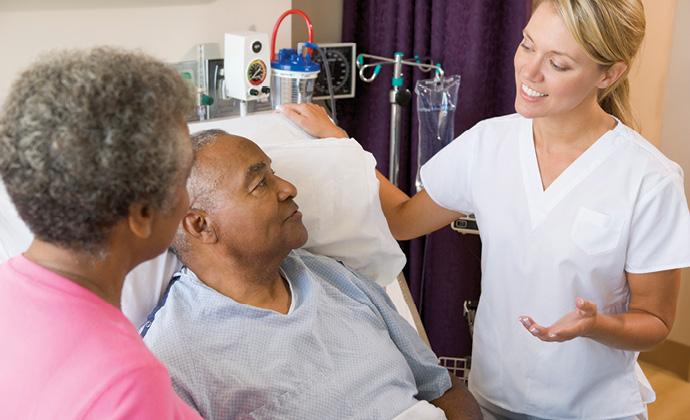 Nakikipag-usap ang isang healthcare professionalsa isang lalaking nakahiga sa kama at sa kanyang asawa