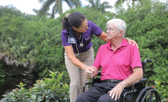 Un cuidador sostiene las manos una mujer sentada en una cama mientras hablan con un médico de VITAS