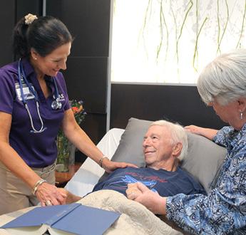 一位躺在病床上的患者正在和VITAS團隊成員交談,身旁立者是他的妻子。