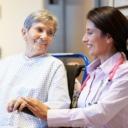 Médica de VITAS le sonríe a su paciente en silla de ruedas