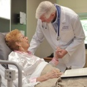 A VITAS physician talks with a woman in an inpatient unit bed