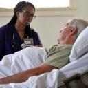 Enfermera de VITAS junto a la cama de un paciente que está en su hogar