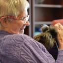 May hawak na miniature Schnauzer ang pasyente ng hospice