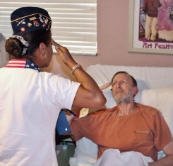 Danny Kessler, Army veteran, is saluted by Broward Volunteer Manager Veronica Palomino in the presence of family and hospice caregivers in the patient's home.