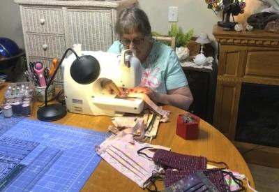 Una voluntaria de VITAS trabaja con su máquina de coser para hacer mascarillas de tela